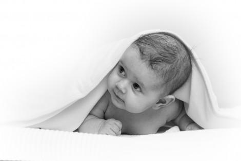 Schwarz weiß Bild eines Babies dass unter einer Decke hervor guckt