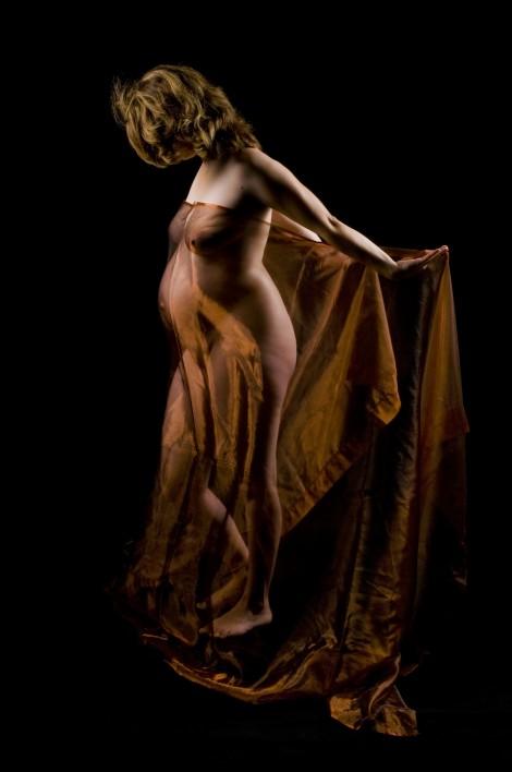 Schwangerschaftsportrait einer Frau von der Seite vor schwarzem Hintergund, Akt, mit Tüchern bedeckt, Kopf geneigt - nicht erkennbar