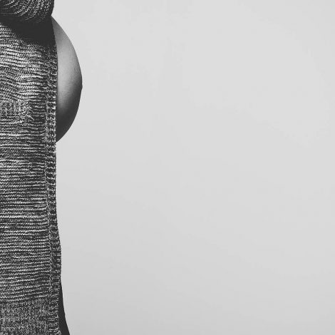 Babybauchfotografie, quadratischer Ausschnitt eines Schwangerenbauchs, Bilddetail am rechten Bildrand, schwarz-weiss-Fotografie, Torso